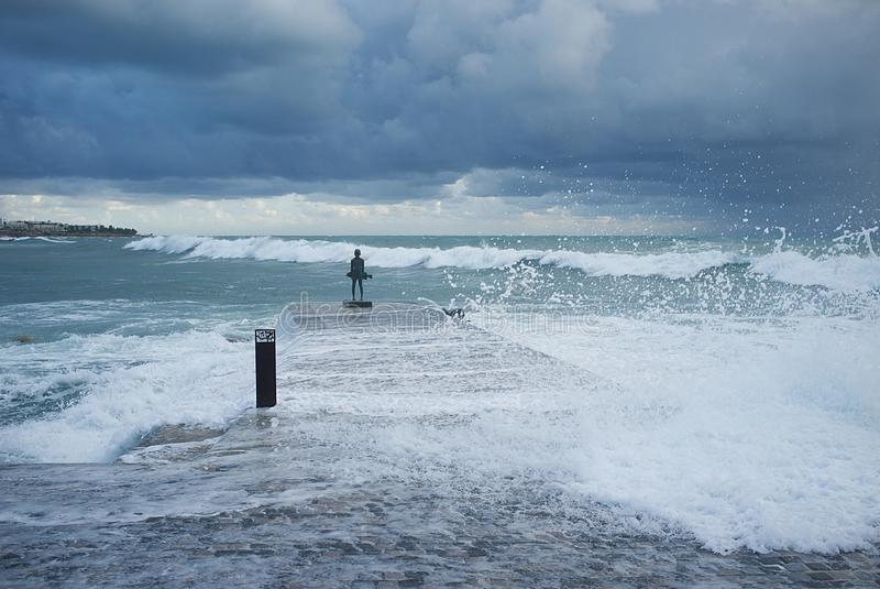 Ställning av en ung fiskare i vågorna arkivbild