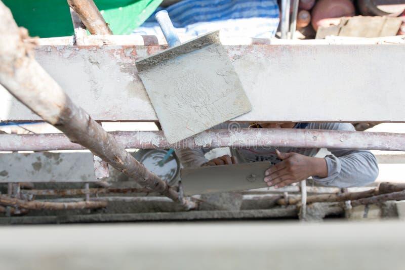 Ställning för arbetare för man för stuckatörcementbetong på ställningwoodl som rappar väggen av huset för bostads- konstruktion fotografering för bildbyråer