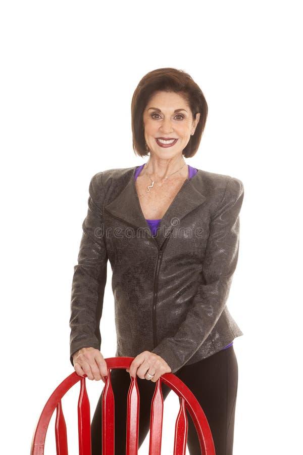 Ställning för kvinnagrå färgomslag bak röd stol fotografering för bildbyråer