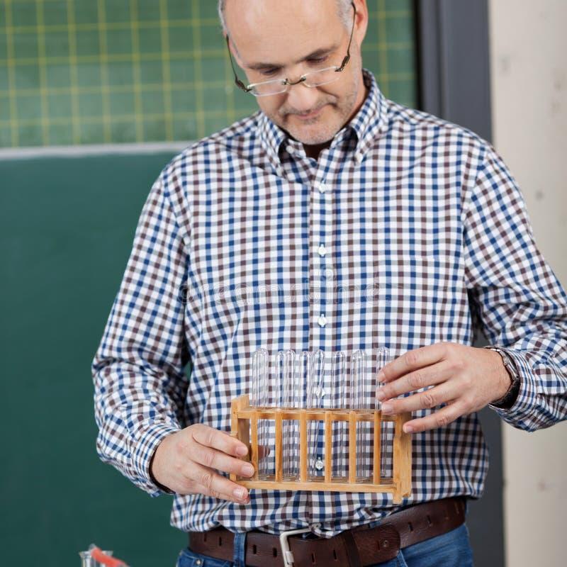 Ställning för professor Holding Test Tube arkivbild