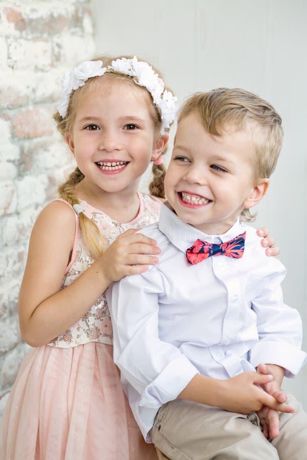 Ställning för två charmig barn som har sammanfogat händer arkivfoto