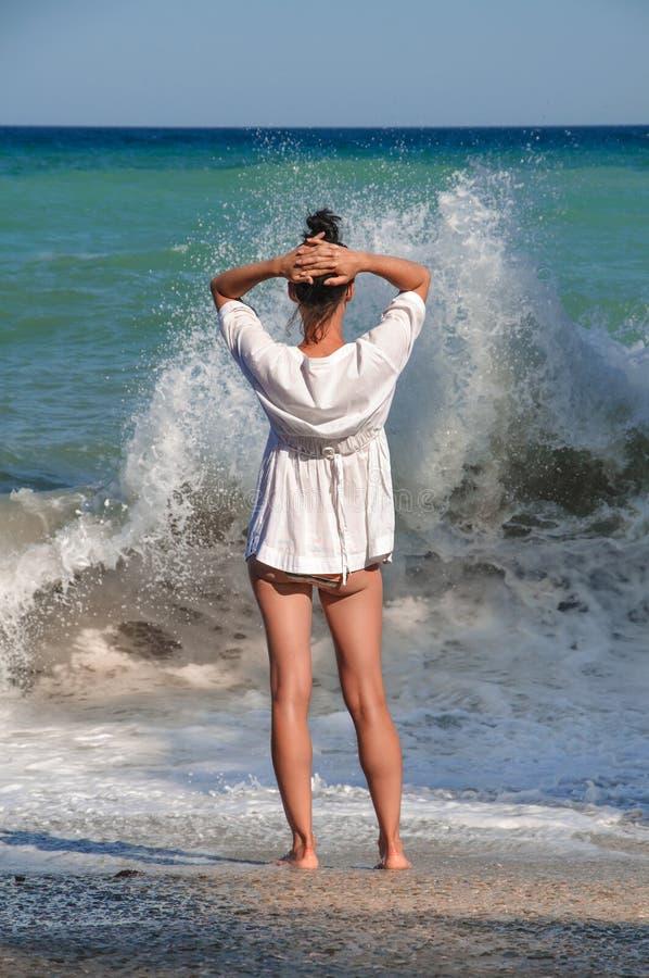 Ställningar för ung kvinna på havet sätter på land och blickar på arkivfoton