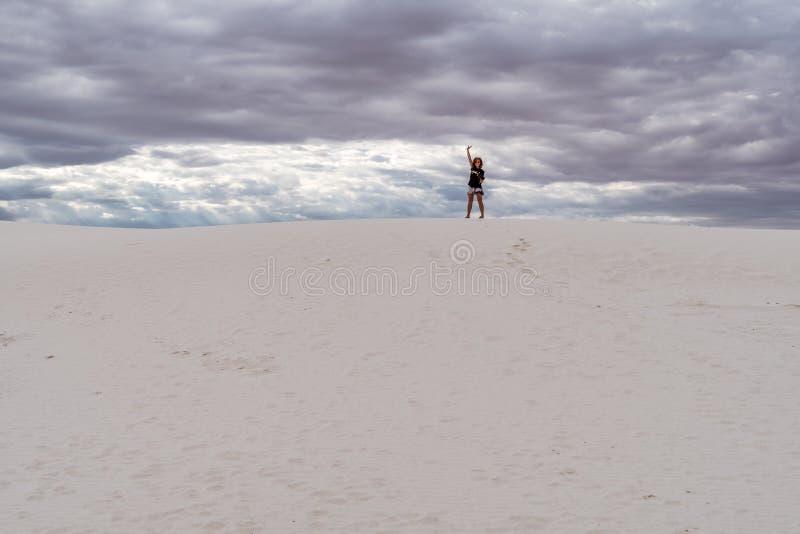 Ställningar för vuxen kvinnlig överst av sanddyn i avståndet arkivbild