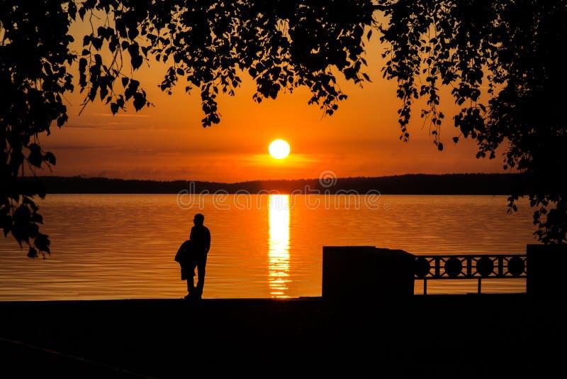 Ställningar och blick på solnedgången eller soluppgång för en ung man vid sjön royaltyfri foto