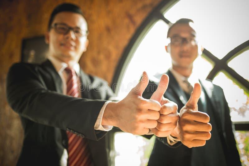 Ställningen och showen för två affärsman tummar upp deras hand till demonstrering av deras överenskommelse att underteckna överen arkivbild