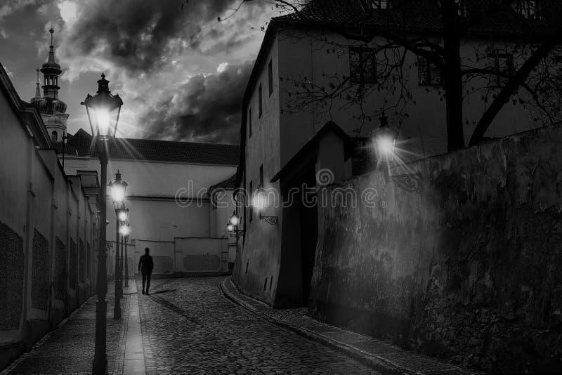 Stämningsmättad smal gränd av Prague på skymning, med gataljus på och konturn av en man som går på kullerstarna royaltyfri fotografi
