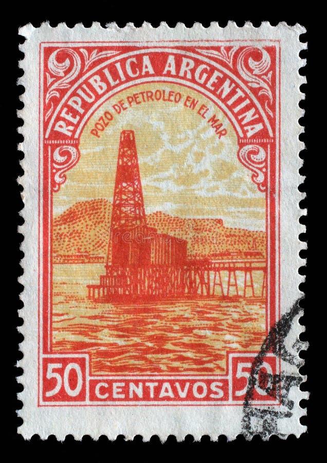 Stämpeln som skrivs ut i Argentina, visar den olje- brunnen royaltyfri fotografi