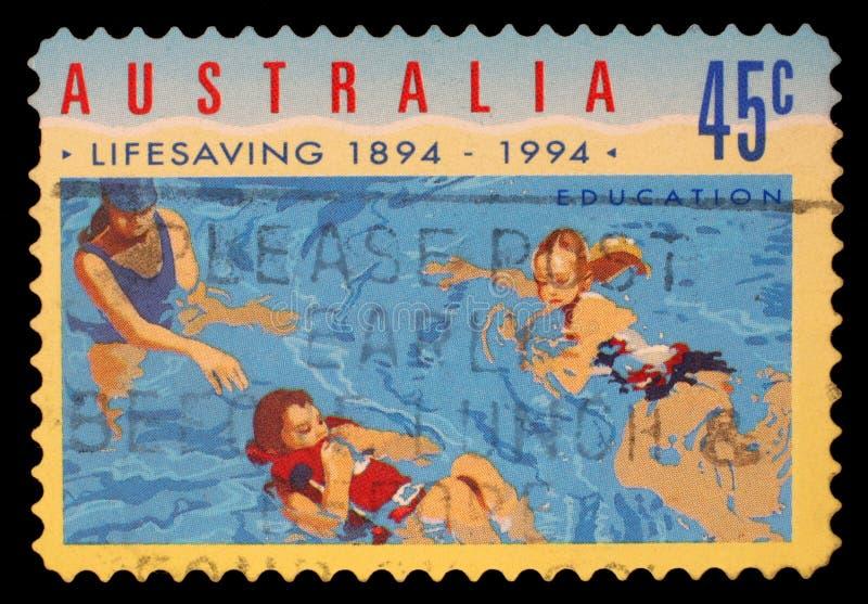 Stämpeln som skrivs ut i Australien, visar folket i vatten, hundraårsdag av den organiserade Liv-besparingen i Australien arkivfoto