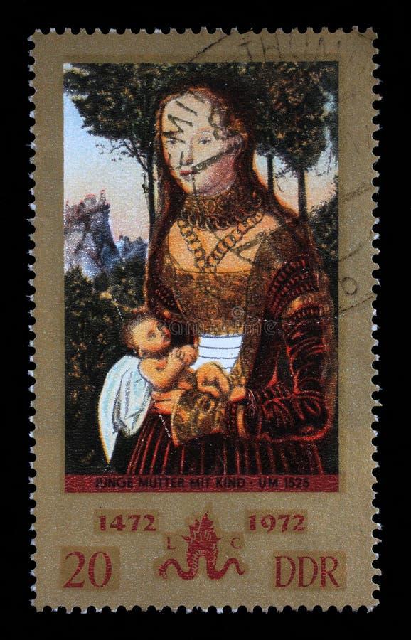 Stämpeln som skrivs ut i GDR, visar barnmodern med barnet av Lucas Cra royaltyfri fotografi