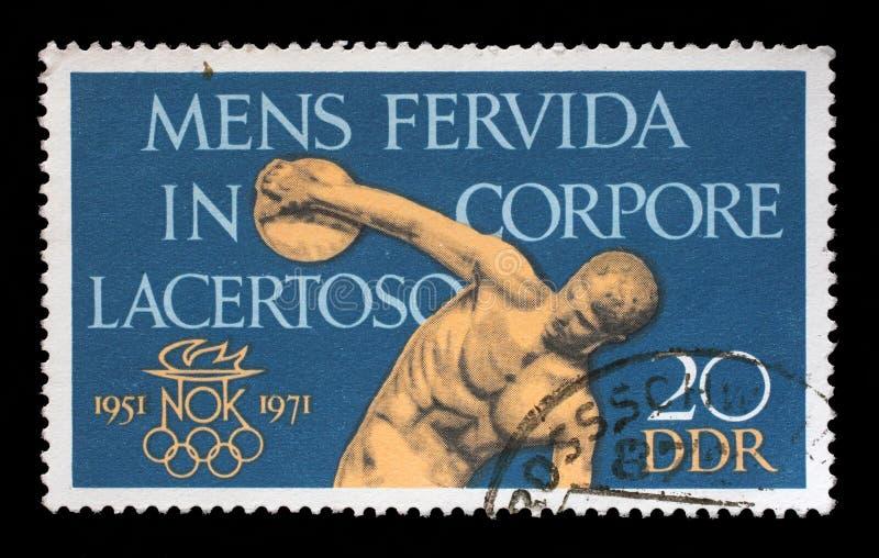 Stämpeln som skrivs ut i GDR, visar den 20th årsdagen av kommittén för OS:en för DDR-` s arkivbilder