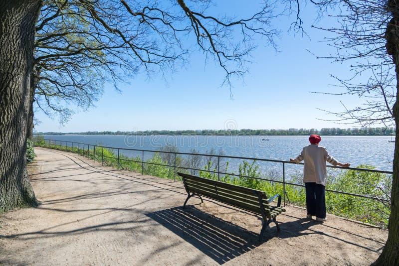 Stände der älteren Frau auf der Elbe-Bank und Blicke in den Abstand lizenzfreie stockfotos
