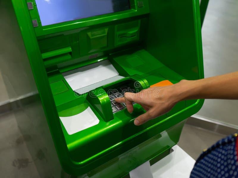 Stäng av handnålen vid en ATM Finger håller på att trycka på en knappnålkod på en knappsats royaltyfri bild