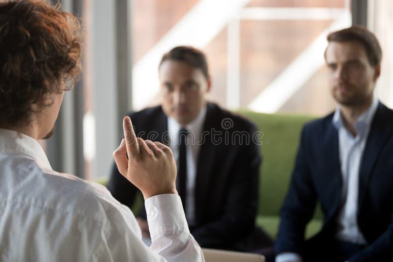 Stäng en säker kandidat som svarar på frågor från cheferna i intervjun royaltyfria foton
