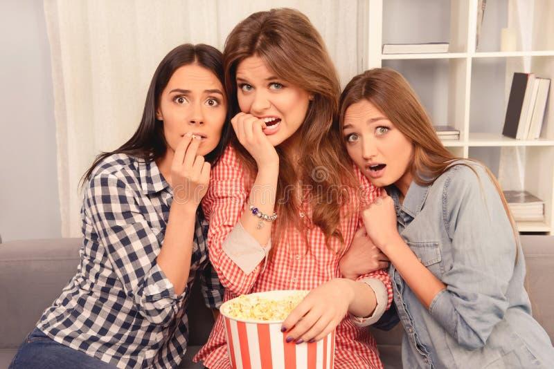 Stäng foto på rädda flickor som väntar på film och äter popcorn royaltyfria bilder