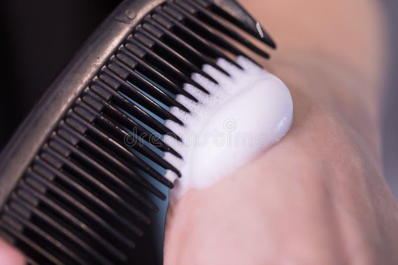 Stäng fotot på skummet i hårborste innan du kombinerar klientens hår arkivfoton