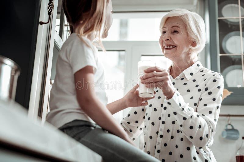Stäng sig av att le den höga kvinnan som ger exponeringsglas av, mjölkar upp till flickan arkivfoto