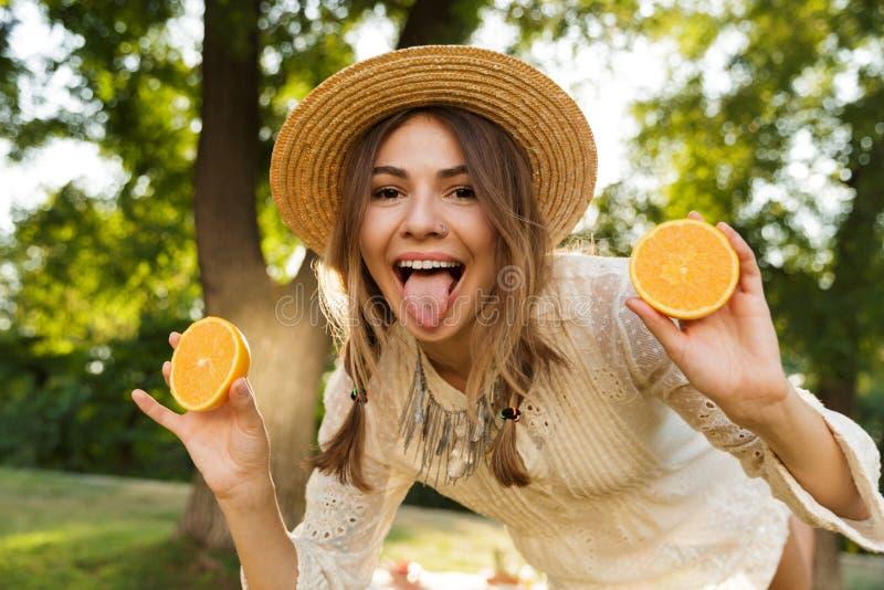 Stäng sig av att le unga flickan i sommarhatt som spenderar tid på, parkerar upp och att visa den skivade apelsinen, arkivbild