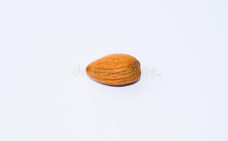 Stäng sig av den bruna mandeln kärnar ur upp isolerat på vit bakgrund royaltyfri fotografi