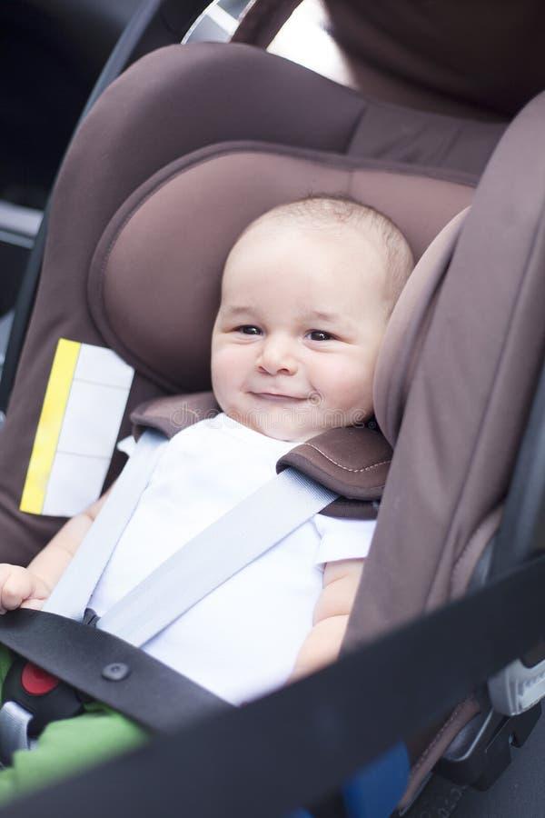 Stäng sig av lite behandla som ett barn upp pojken i en bil i en barnplats arkivbilder