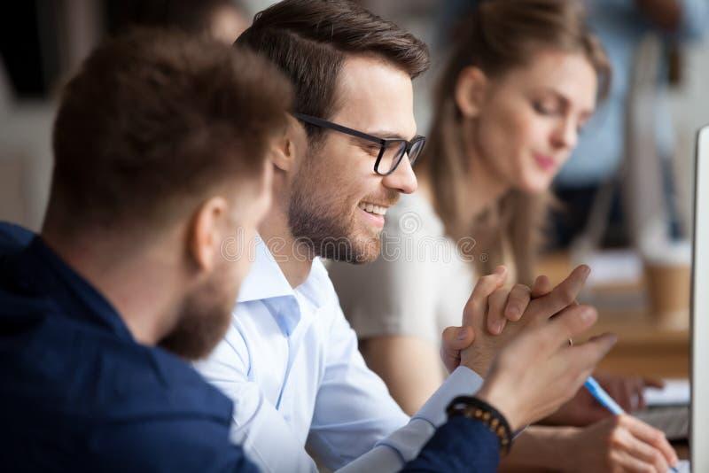 Stäng sig av manliga kollegor skrattar upp att arbeta på PC:n royaltyfria foton