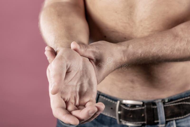 Stäng sig av mannen som lider från, smärtar upp i hans handled på rosa bakgrund sjukvård- och problembegrepp arkivfoto