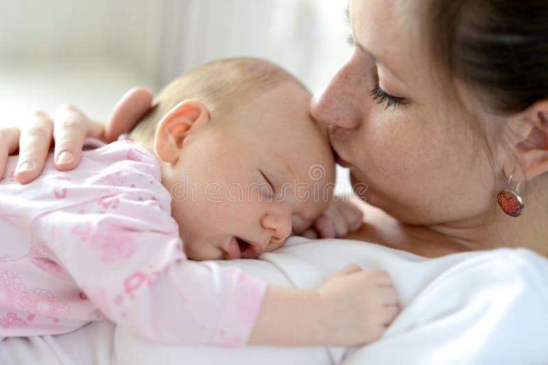 Stäng sig av modern som rymmer hennes gulligt, behandla som ett barn upp dottern royaltyfria foton