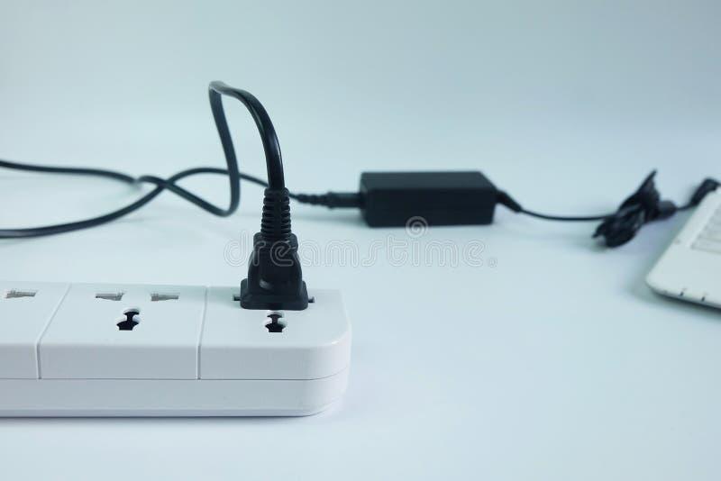 Stäng sig pluggar upp in uppladdaren för adaptermaktkabel med den suddiga bärbar datordatoren på vit royaltyfri bild
