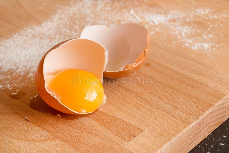 Stäng sig upp ägget, äggula i äggskalet, mjöl på en träbakgrund arkivbilder