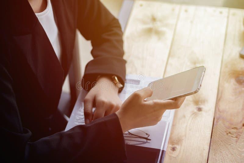 Stäng sig upp affärskvinnan som använder smartphonen, medan sitta att koppla av arkivbilder