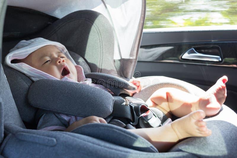 Stäng sig upp asiatiskt gulligt nyfött behandla som ett barn sammanträde i modernt bilsäte arkivbilder