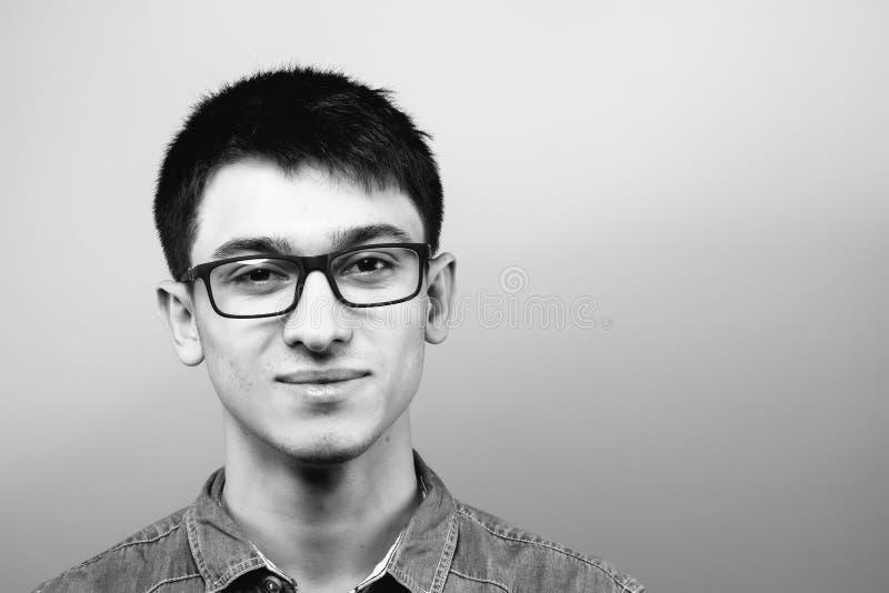 Stäng sig upp att le den unga affärsmannen Wearing Eyeglasses som ser kameran mot Gray Wall Background med kopieringsutrymme arkivbilder