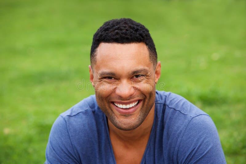 Stäng sig upp att le sammanträde för ung man utomhus mot grönt gräs arkivfoto