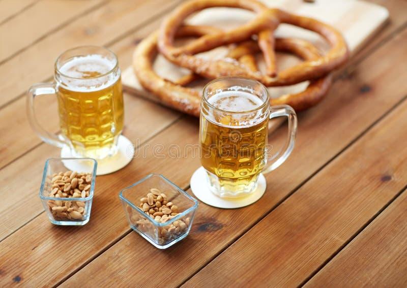 Stäng sig upp av öl, kringlor och jordnötter på tabellen arkivfoto