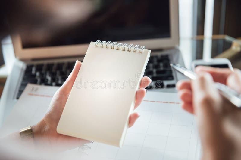 Stäng sig upp av affärskvinnans händer genom att använda bärbara datorn och skriva i anteckningsbok royaltyfri foto