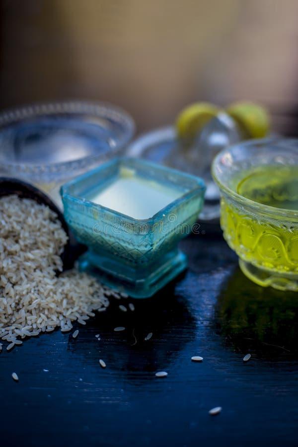 Stäng sig upp av ansiktsmask av rismjöl med grönt te, vatten och citronjuice på träyttersida i en exponeringsglasbunke med några  royaltyfri fotografi