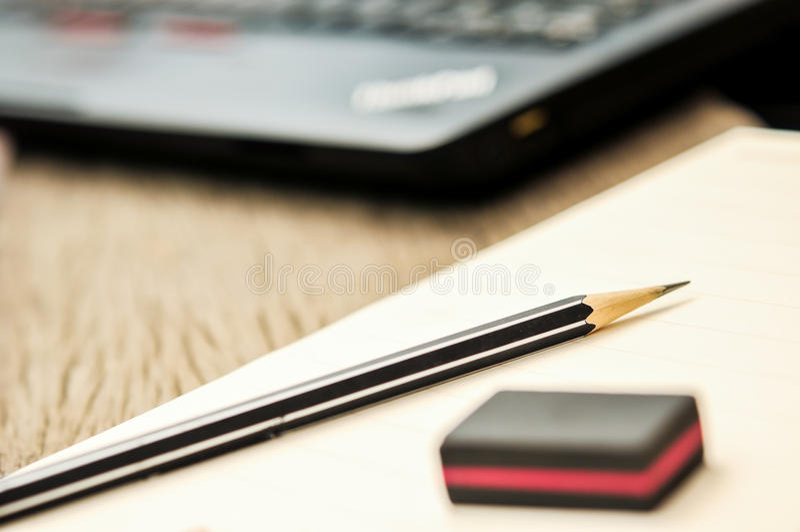 Stäng sig upp av anteckningsboken med blyertspennan och radergummit överst royaltyfri foto