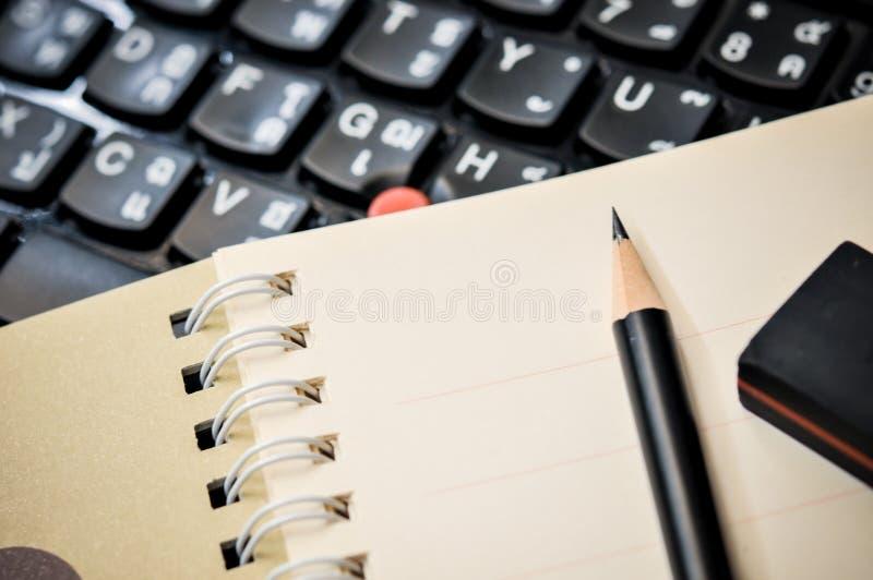 Stäng sig upp av anteckningsboken med blyertspennan och radergummit överst royaltyfri fotografi