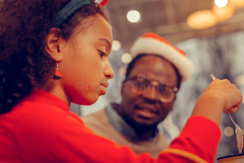 Stäng sig upp av att appellera dottern som dricker kakao med hennes farsa arkivfoto