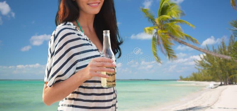 Stäng sig upp av att le den unga kvinnan som dricker på stranden fotografering för bildbyråer