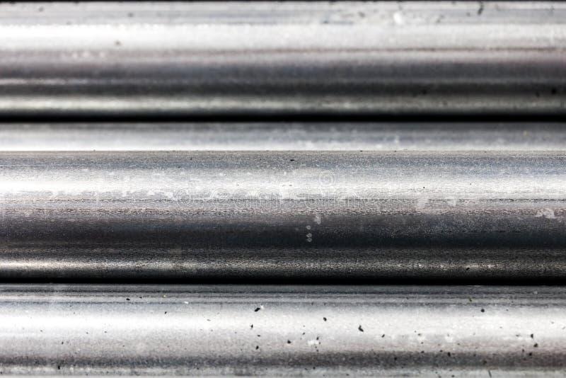 Stäng sig upp av avsnitt av stålrör som överst staplas av de/texturerad metallisk bakgrund royaltyfri bild