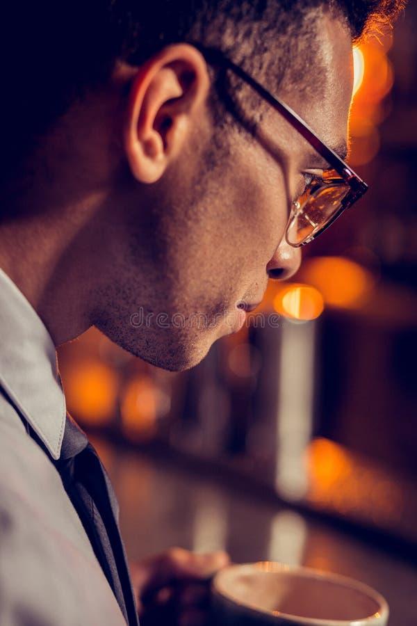 Stäng sig upp av bärande exponeringsglas för den stiliga mörker-haired affärsmannen arkivfoto