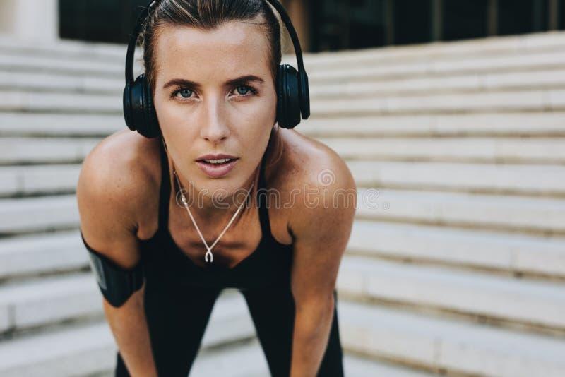 Stäng sig upp av bärande hörlurar för en kvinnaidrottsman nenutbildning arkivbild
