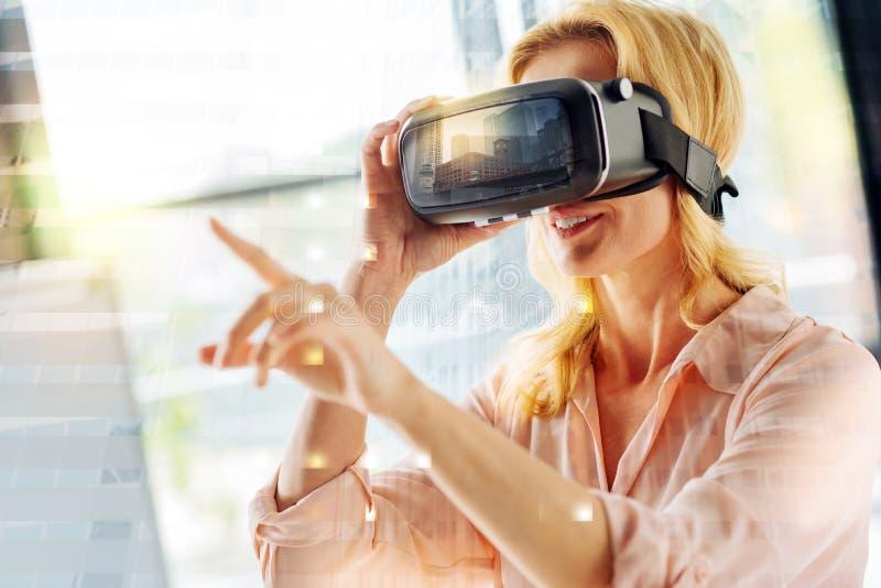 Stäng sig upp av bärande virtuell verklighetexponeringsglas för den upphetsade kvinnan arkivbild