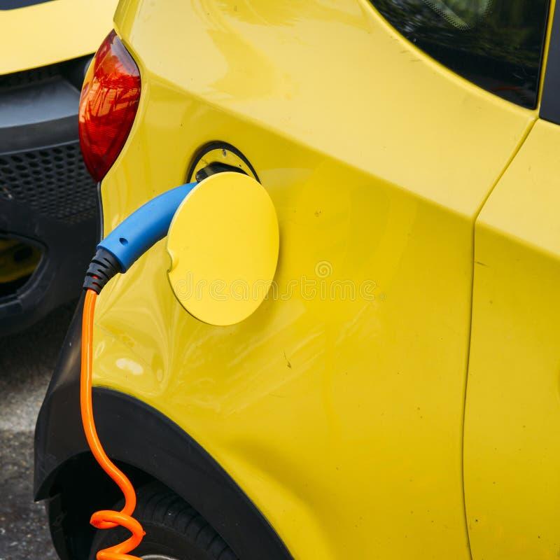 Stäng sig upp av bilen som elektroniskt laddas på en offentlig uppladdningsbar skeppsdockastation fotografering för bildbyråer
