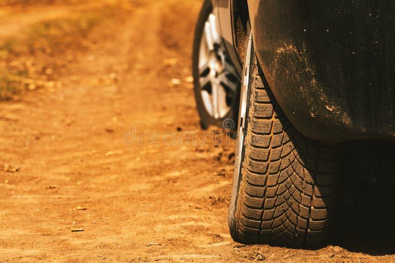 Stäng sig upp av bilgummihjul på smutslandsvägen royaltyfri bild