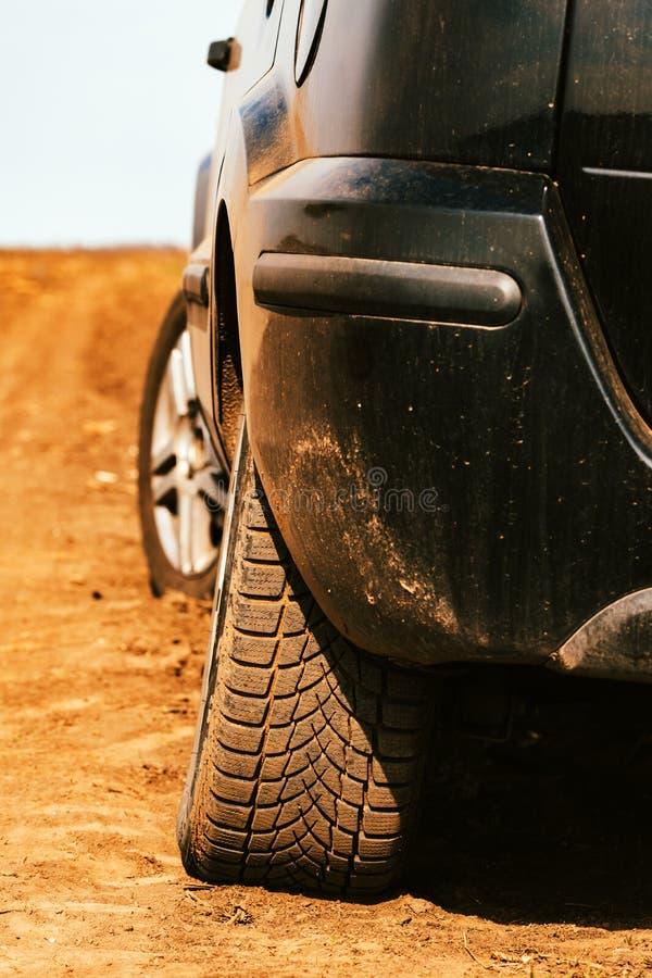 Stäng sig upp av bilgummihjul på smutslandsvägen fotografering för bildbyråer
