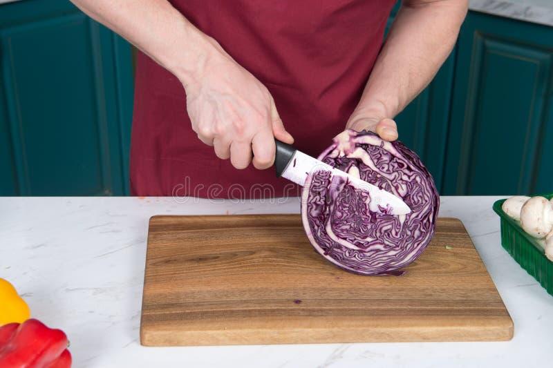 Stäng sig upp av bitande halva av röd kål Closeup av manhänder med kniven och röd kål Röd kål på träskärbräda arkivfoton