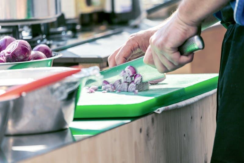 Stäng sig upp av bitande lökar för den oigenkännliga kocken och andra grönsaker med kockkniven, medan arbeta fotografering för bildbyråer