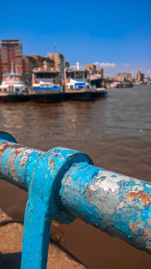 Stäng sig upp av blåa Rusty Metal Pier Fence royaltyfri foto