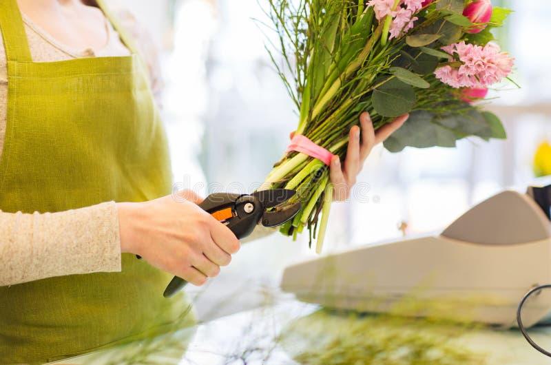 Stäng sig upp av blomsterhandlarekvinna med blommor och pruner arkivbild